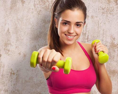 kvinna tränar armarna med hantlar