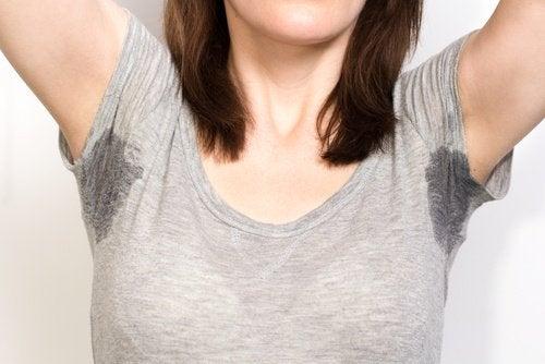 kvinna har två stora svettfläckar under armarna