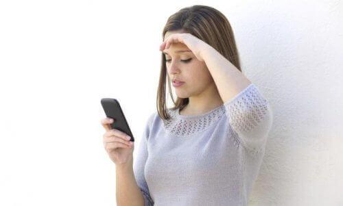 Kvinna läser meddelanden på sin mobil