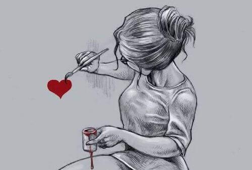 Flicka målar ett hjärta på väggen
