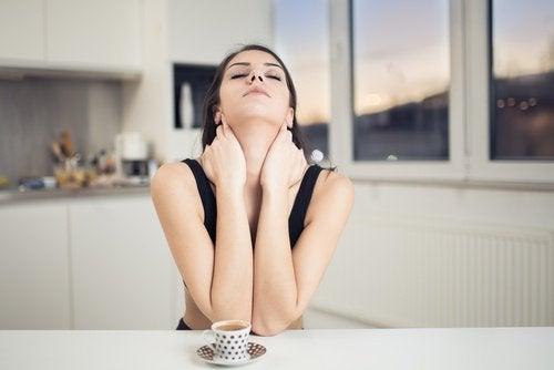 Kvinna stretchar nacken med en kopp te