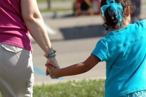 Barn håller hand med någon