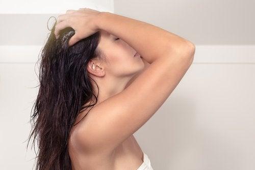 kvinna masserar hårbotten