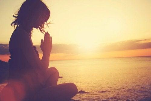 Kvinna mediterar i solnedgången