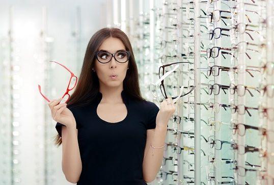 Kvinna med beslutsångest över vilka glasögon hon ska köpa