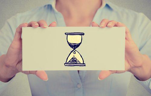 Man håller upp skylt med ett timglas