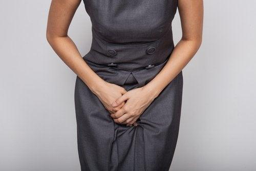 Kvinna med klänning och smärta i magen