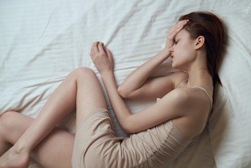 Trött kvinna i sängen