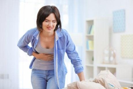 kvinna grimaserar och håller sig för magen