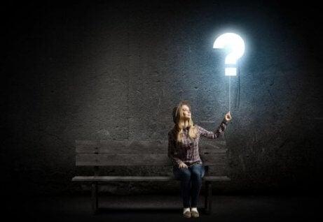 kvinna som håller i ett upplyst frågetecken