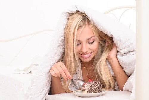 Kvinna äter tårta i sängen
