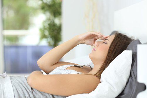 Kvinna som ligger i sängen och är trött