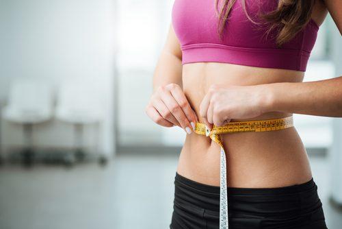 Kvinna som mäter magen