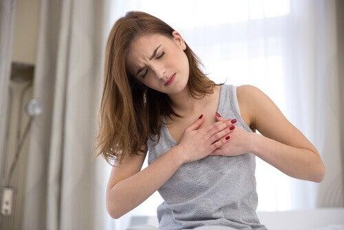 Kvinna som sitter på säng med bröstsmärta
