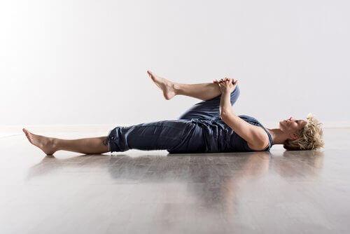 Kvinna som stretchar liggandes på rygg