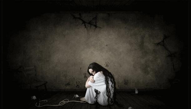 Kvinna som sitter ner i mörkt rum
