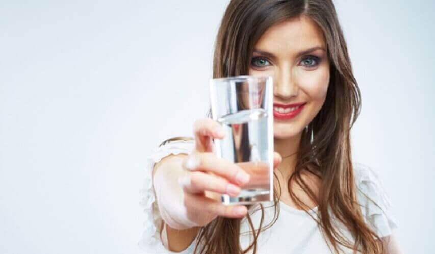 Kvinna med ett glas vatten