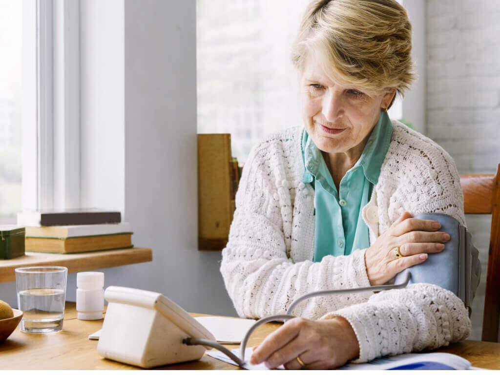 Kvinna som mäter blodtrycket