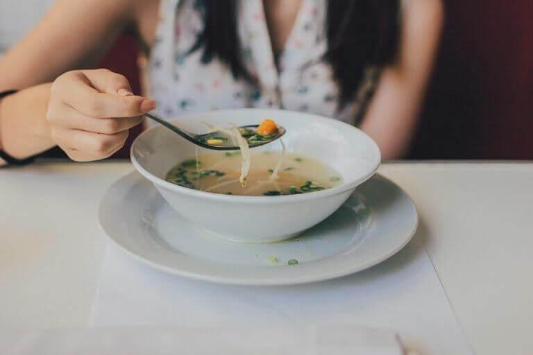 Kvinna som äter soppa