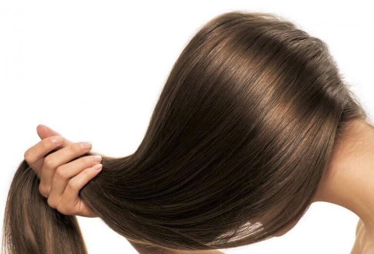 Kvinna som håller sitt hår