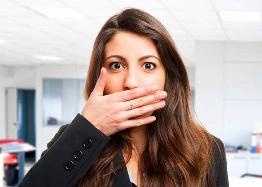 Kvinna som håller handen för munnen