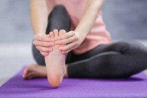 Kvinna som masserar foten