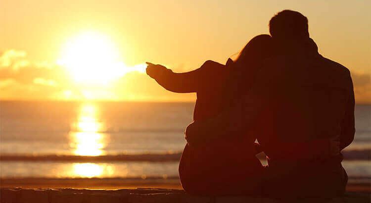 Par som njuter av solnedgången på stranden