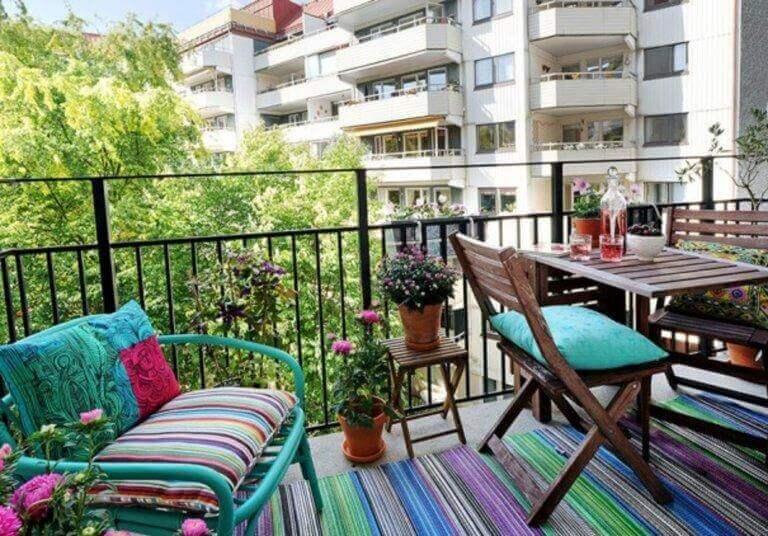 Färgglad balkong i grönt stadsområde.