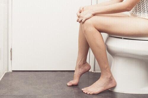 Kvinna-som-sitter-på-toaletten.
