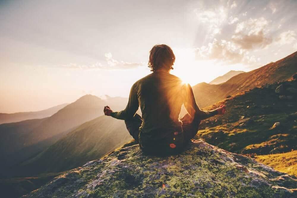 Man som mediterar på berg.