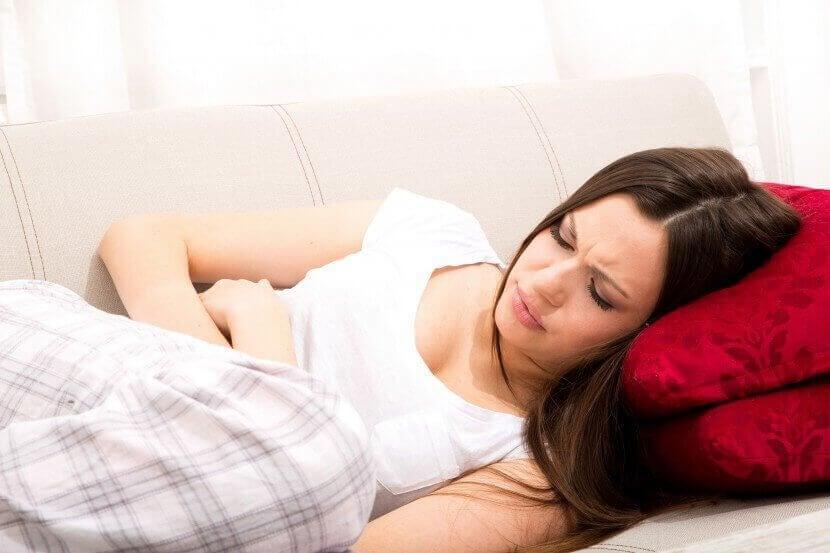 Kvinna med magont i soffan.