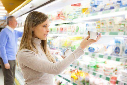 kvinna kollar ingredienserna på yoghurt