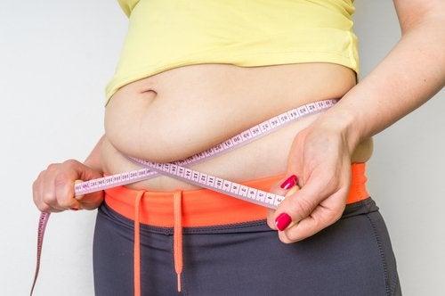 överviktig person med måttband runt magen
