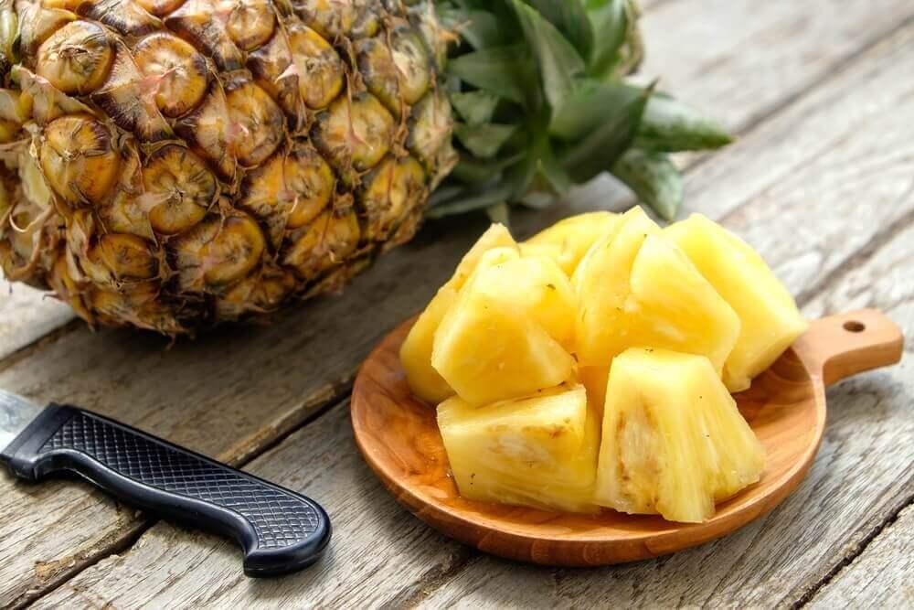 Ananas och kniv på bord.