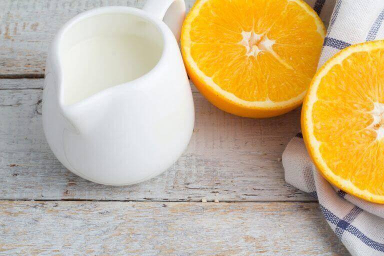 halvad apelsin bredvid en kanna mjölk