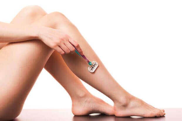 Kvinna som rakar benen.