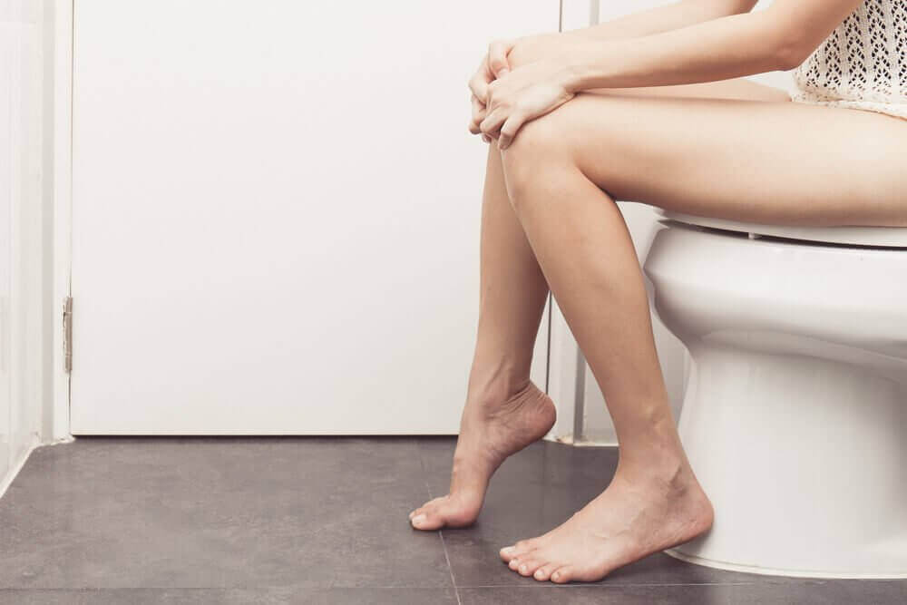Kvinna som sitter på toalett.