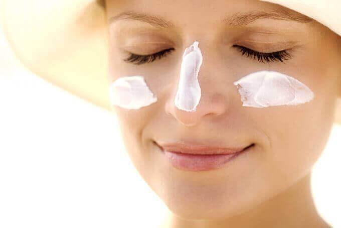 kvinna med solkräm på näsa och kinder