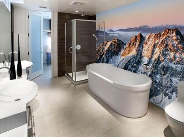 Badkar med berg som motiv på vägg.