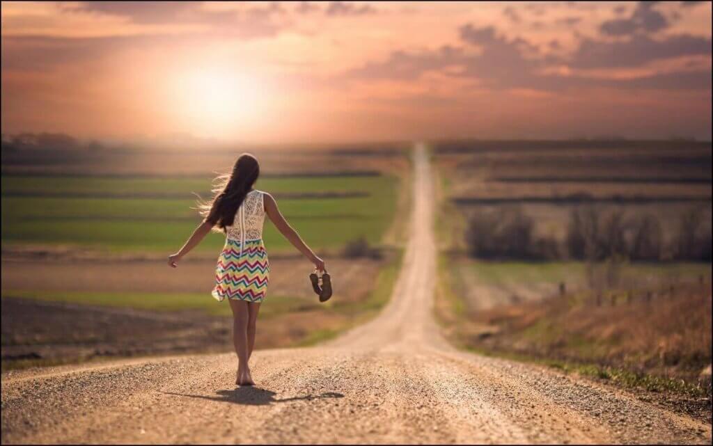 Kvinna som går på landsväg.