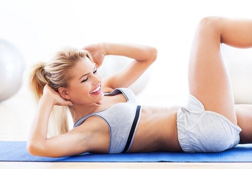 Kvinna som tränar på en blå matta.