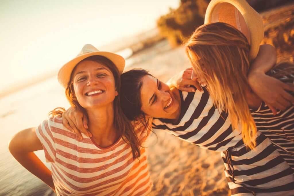 Kvinnor som skrattar på stranden.