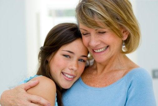 Mamma som kramar dotter.