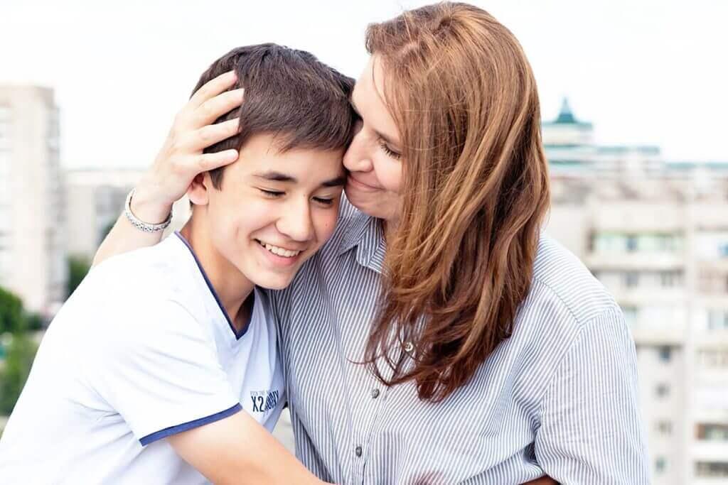 Mamma som kramar son.