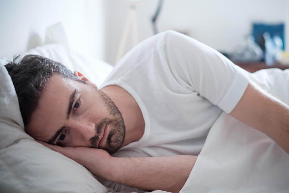 Man som ligger i sängen och ser dyster ut.