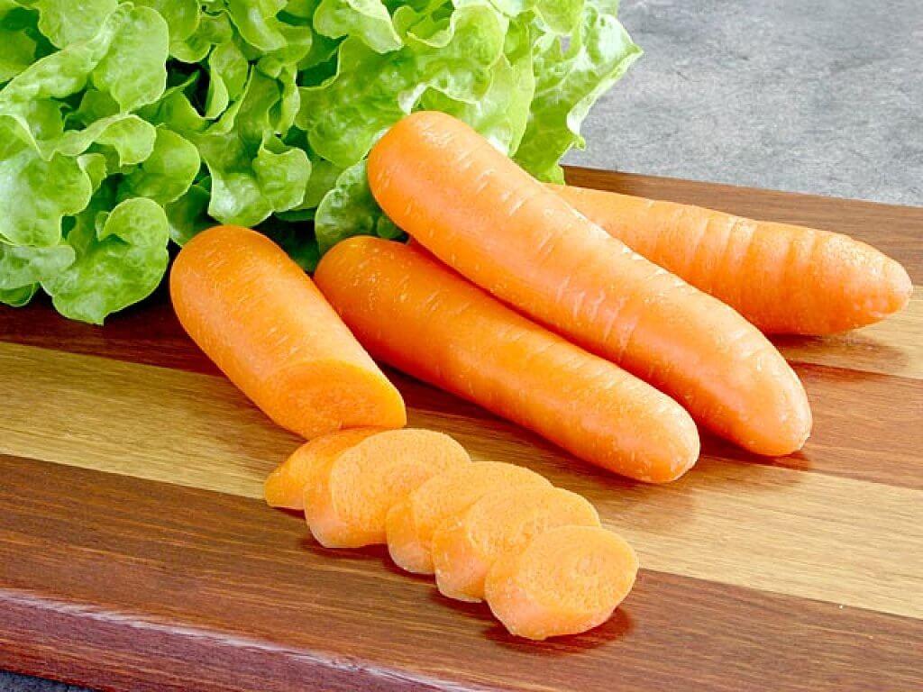 Skivade morötter på skärbräda.