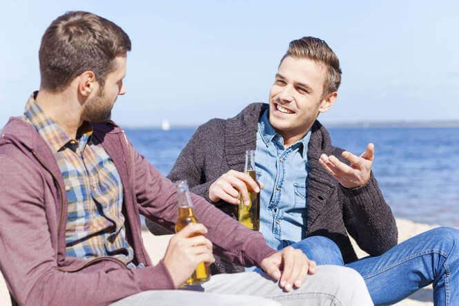 Två män som samtalar vid havet.
