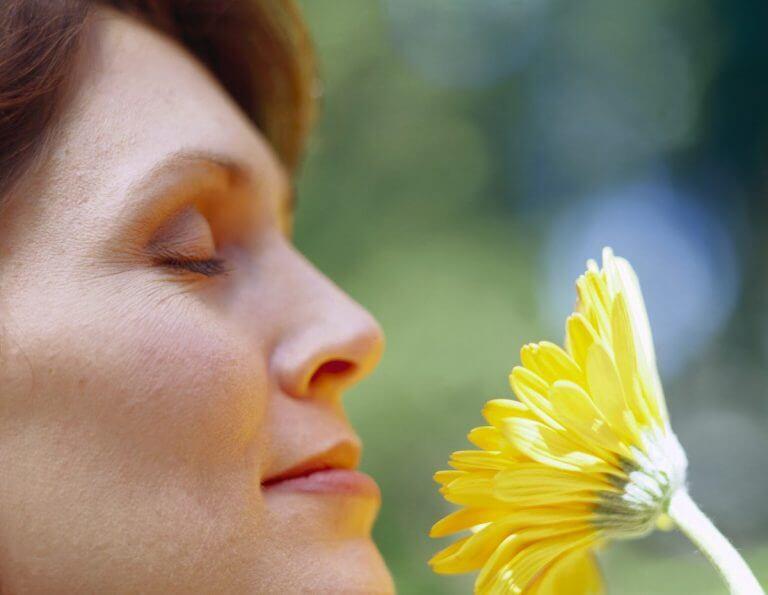 Medelålders kvinna njuter av blomma