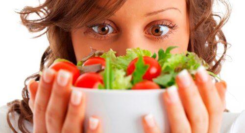 Kvinna som håller upp en skål med grekisk sallad.