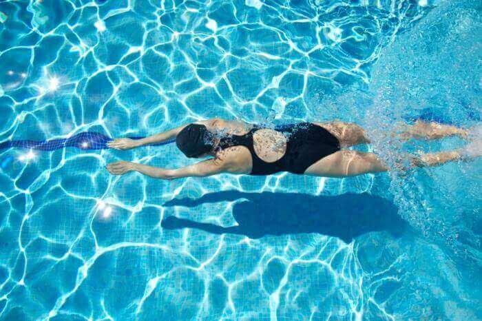 Kvinna som använder tekniker för att simma i en pool.